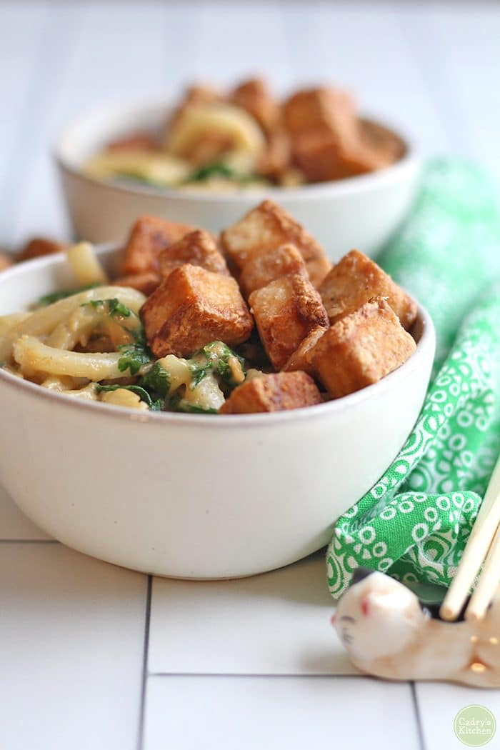 Bowl of peanut butter noodles with spinach, topped with fried hoisin tofu.
