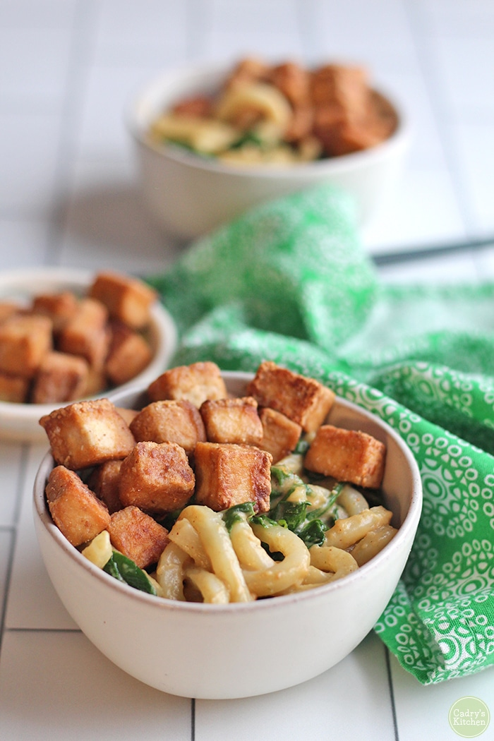 Bowl of peanut butter noodles topped with fried hoisin tofu & sauteed spinach by green napkin.