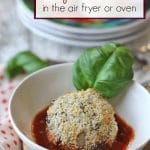 Text: Vegan arancini in the air fryer or oven. Risotto rice ball in marinara with basil leaf.