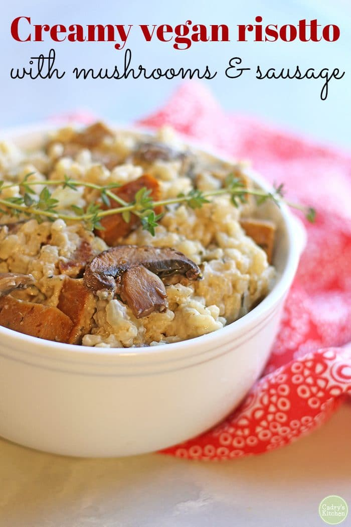 Text: Creamy vegan risotto with mushrooms and sausage. Vegan risotto in bowl with mushrooms and seitan sausage by a red napkin.