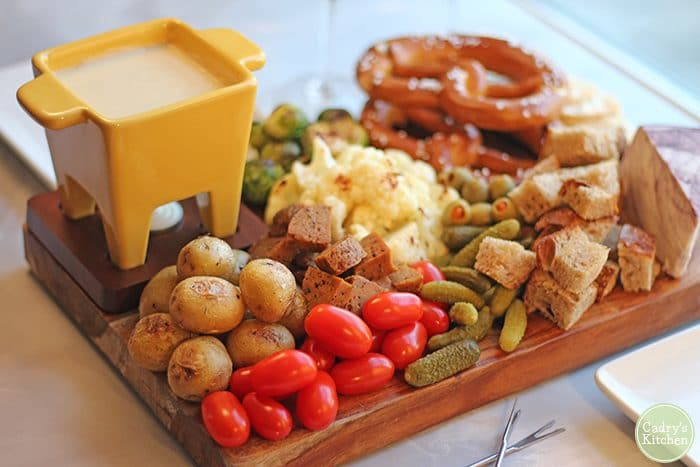 Vegan fondue board with roasted cauliflower, roasted Brussels sprouts, and potatoes.