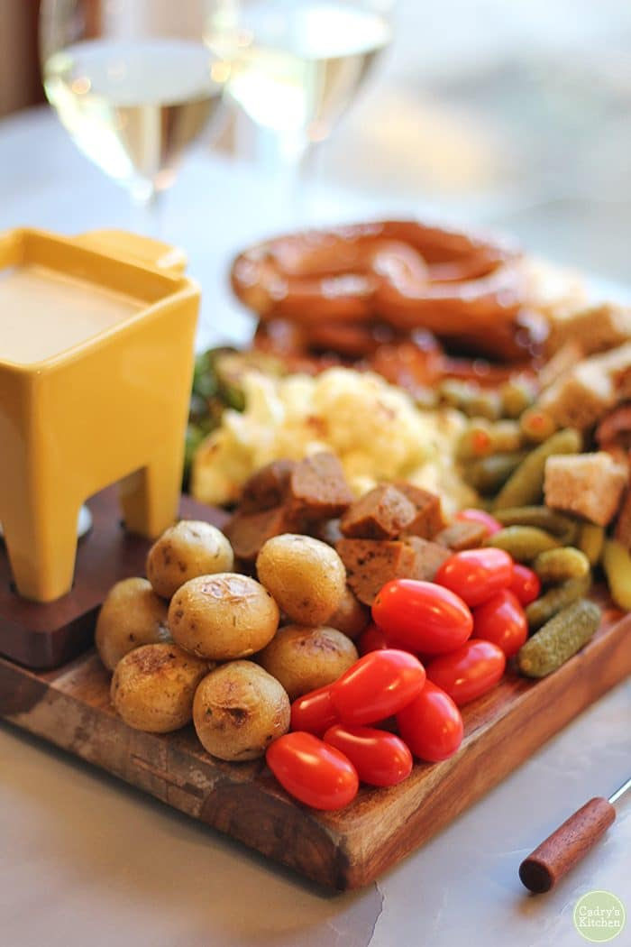 Vegan fondue board with potatoes, tomatoes, and cornichons.