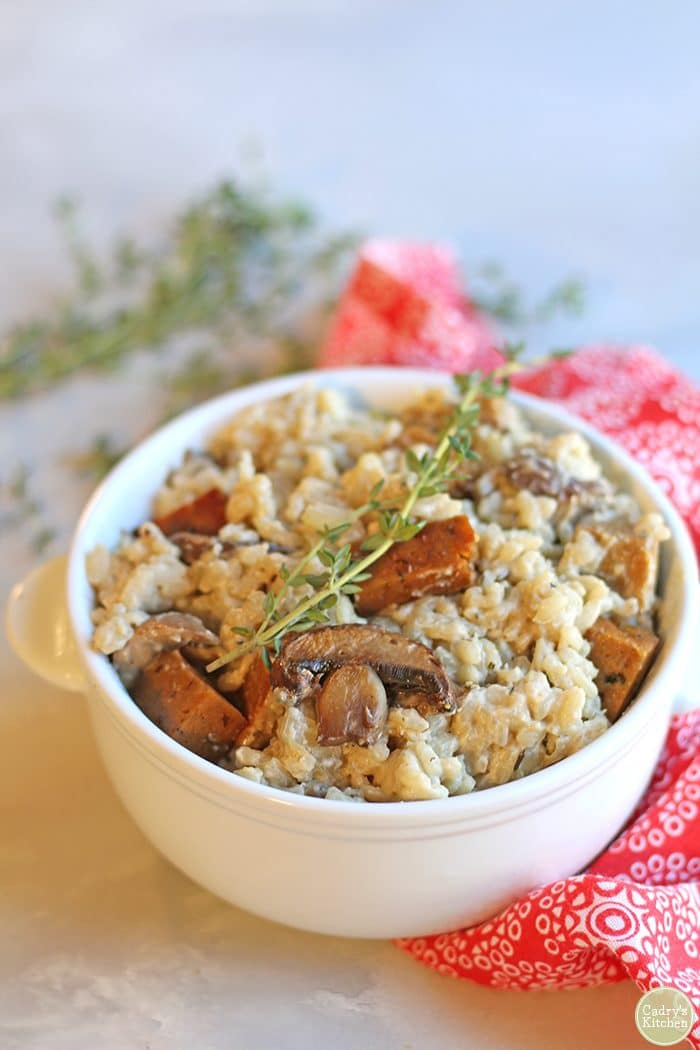 Creamy vegan risotto in bowl with mushrooms and seitan sausage.