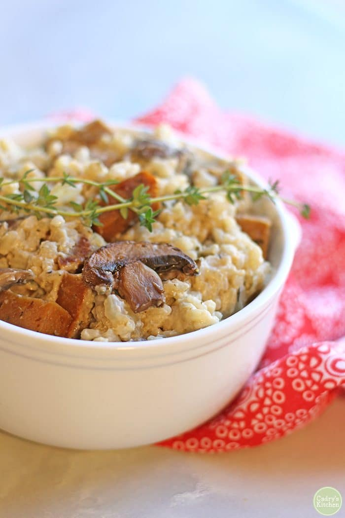 Close up vegan risotto with mushrooms, seitan sausage, and thyme.