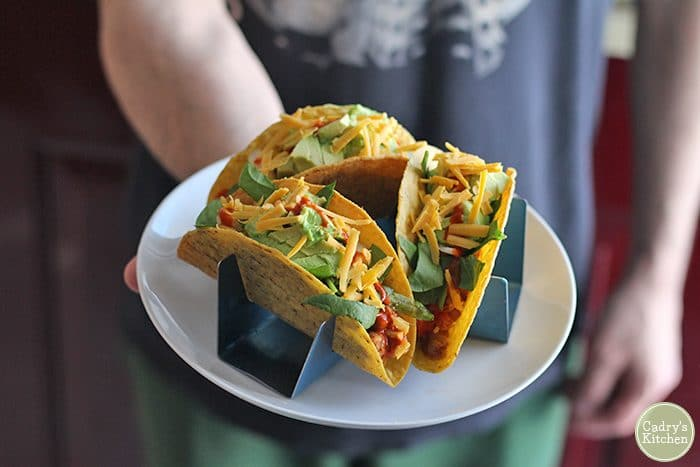 Hand holding chickpea tacos with taco holders.