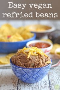 Text: Easy vegan refried beans. Vegan refried beans with non-dairy cheese and onions in blue bowl on white table.