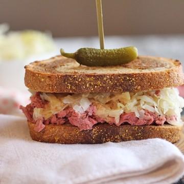 Vegan reuben jackfruit sandwich on board with pickle.