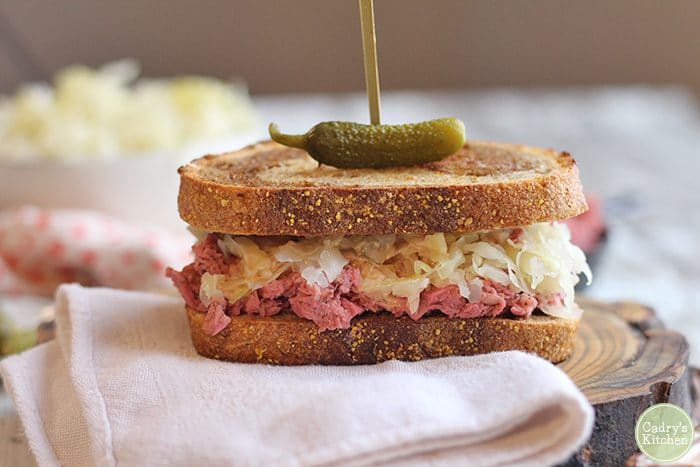 Vegan reuben on board with pickle.