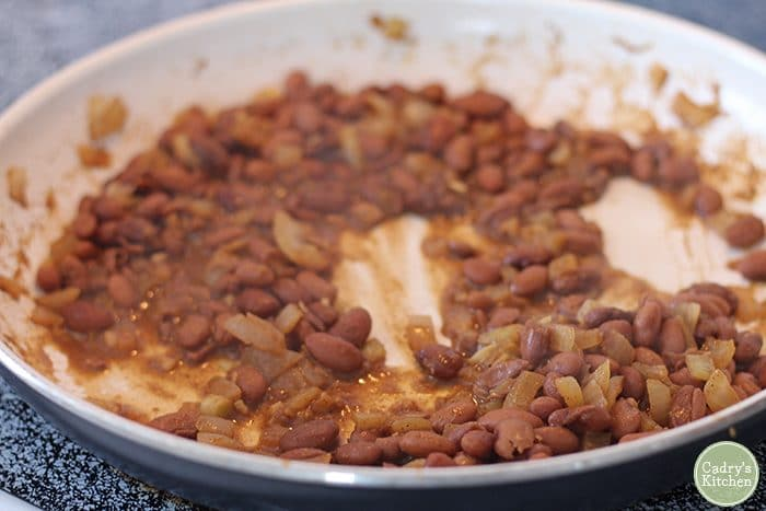 Pinto beans with onions and garlic in skillet.