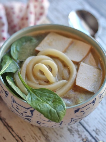 Bowl of udon noodle soup with spinach and tofu.