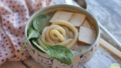 Udon noodle soup with tofu and spinach in bowl.