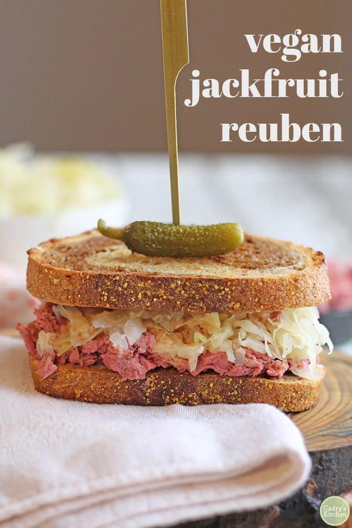 Text: Vegan jackfruit reuben. Jackfruit sandwich on board with napkin.