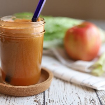 Glass with blue straw holding carrot juice recipe. In background, an apple, celery, carrot, and romaine lettuce.