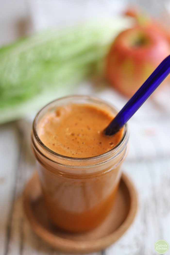 Glass of carrot, apple, lettuce, cucumber, and celery juice in glass with blue straw.