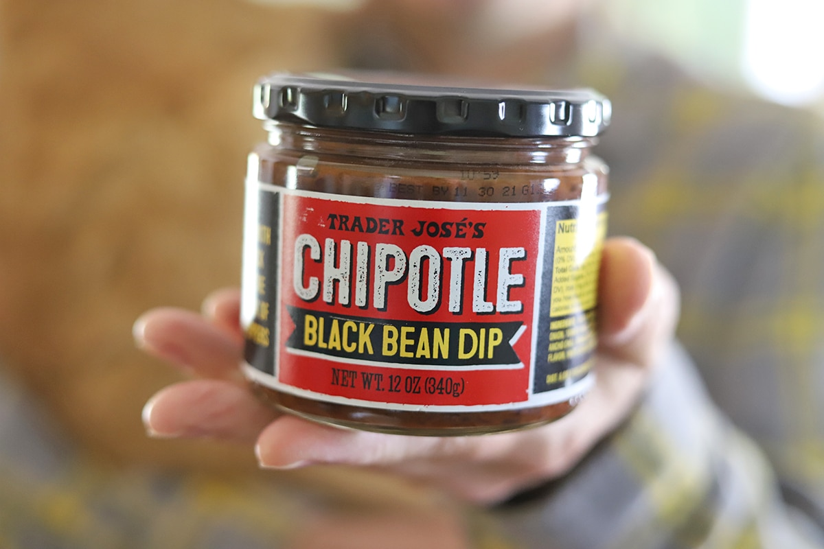 Hand holding chipotle black bean dip.