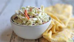 Bowl of vegan coleslaw with yellow napkin on white table.
