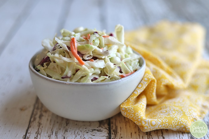 Bowl of vegan coleslaw with yellow napkin on white table.
