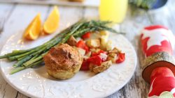 Crustless vegan quiche on plate with roasted potatoes, asparagus, and orange slices.