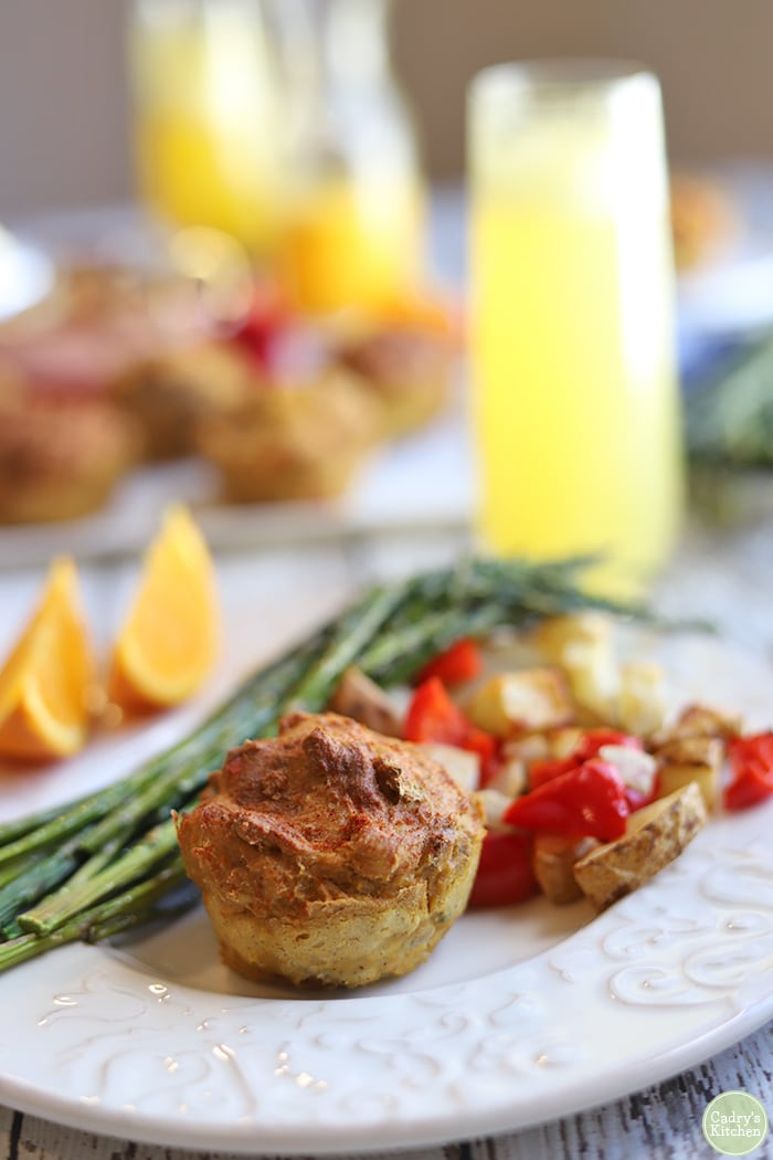 Mini vegan quiche on plate with roasted potatoes, asparagus, and orange slices.