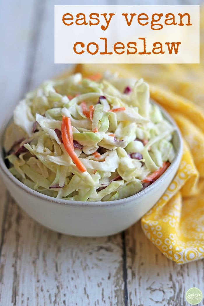 Text: Easy vegan coleslaw. Bowl of vegan coleslaw on white table with yellow napkin.