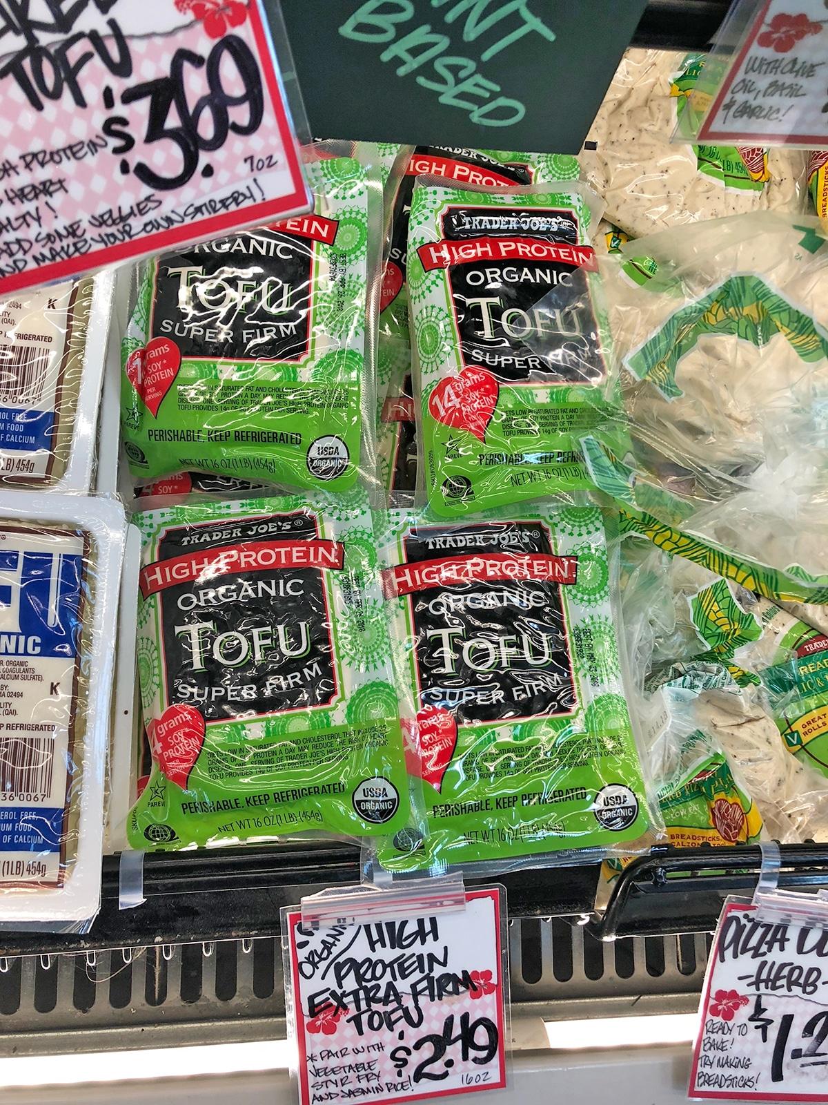 Blocks of super firm tofu in refrigerated case.