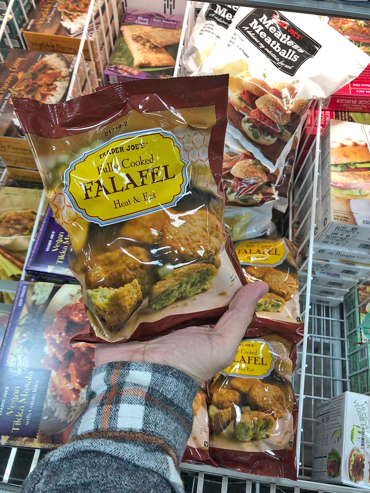 Hand holding bag of frozen falafel.