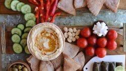Overhead mezze platter with easy hummus recipe, dolmas, cherry tomatoes, vegan feta, and cucumber slices.
