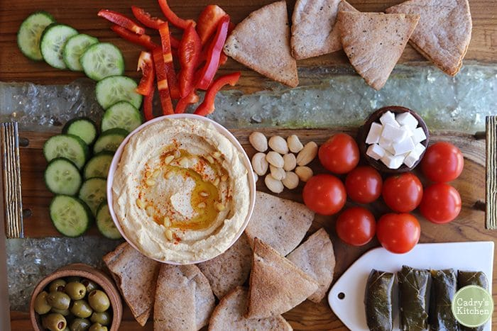 Overhead mezze platter with easy hummus recipe, dolmas, cherry tomatoes, vegan feta, and cucumber slices.