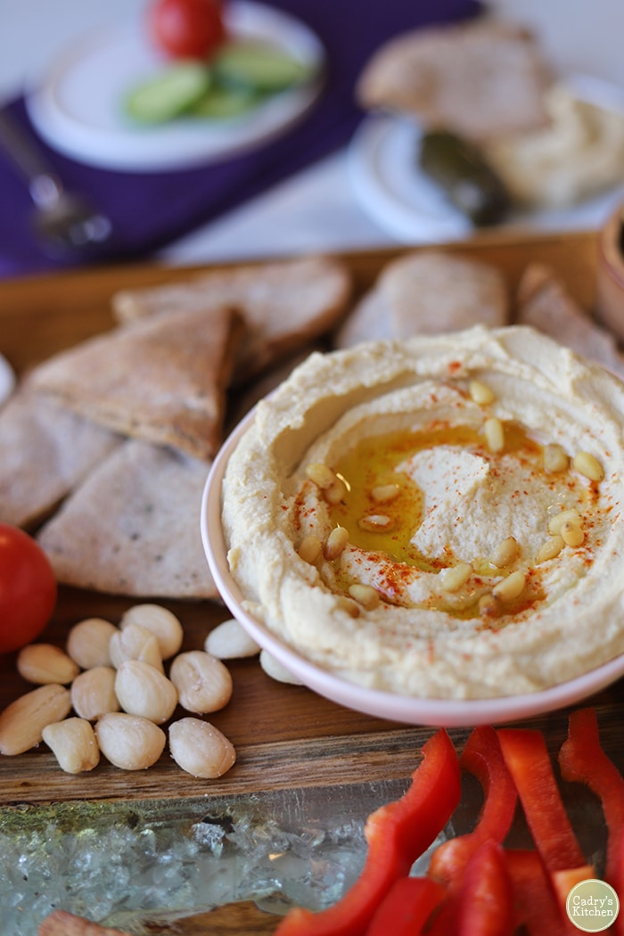Bowl of easy hummus recipe, Marcona almonds, and homemade pita chips on board.