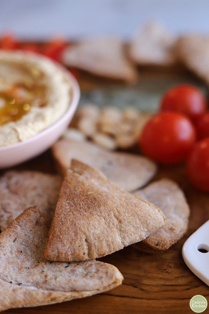 Close-up homemade pita chips on board with hummus, tomatoes, and Marcona almonds.
