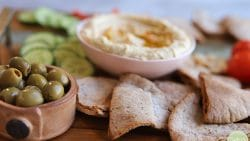 Close-up green olives with pimentos and homemade pita chips.