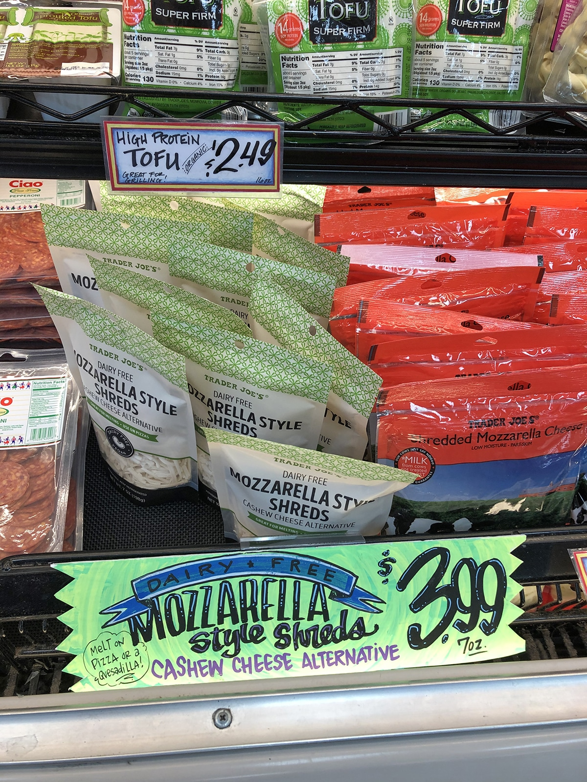 Bags of vegan mozzarella in refrigerated case.