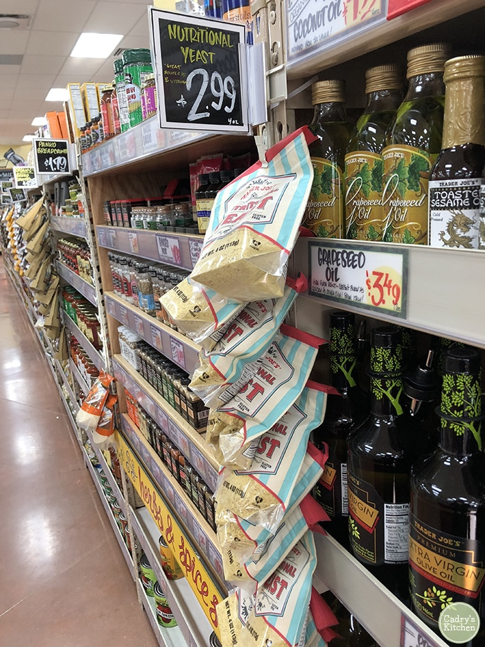 Nutritional yeast flakes hanging on store shelves at Trader Joe's.