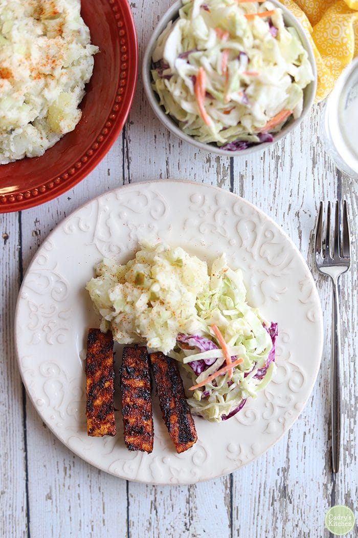 Overhead plate with vegan coleslaw, potato salad, and barbecued tofu.