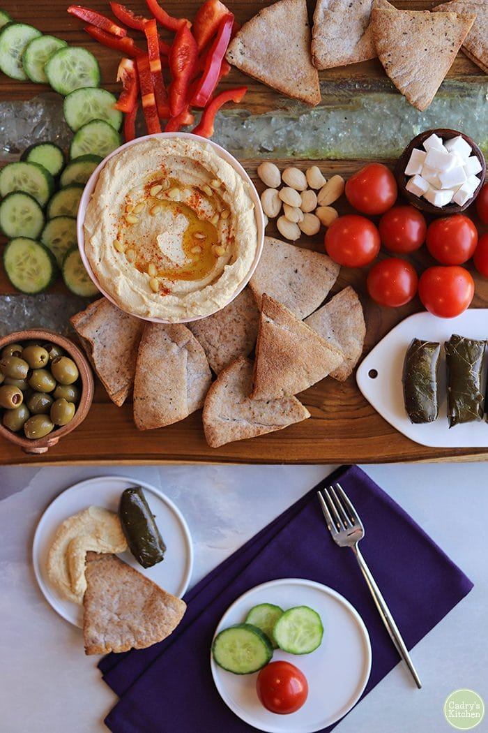 Overhead board with hummus, cucumbers, olives, dolmas, homemade pita chips, and purple napkin.