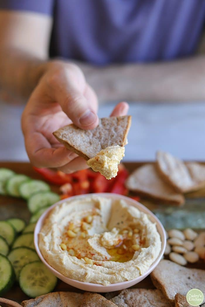 Hand dipping homemade pita chip into bowl of hummus.