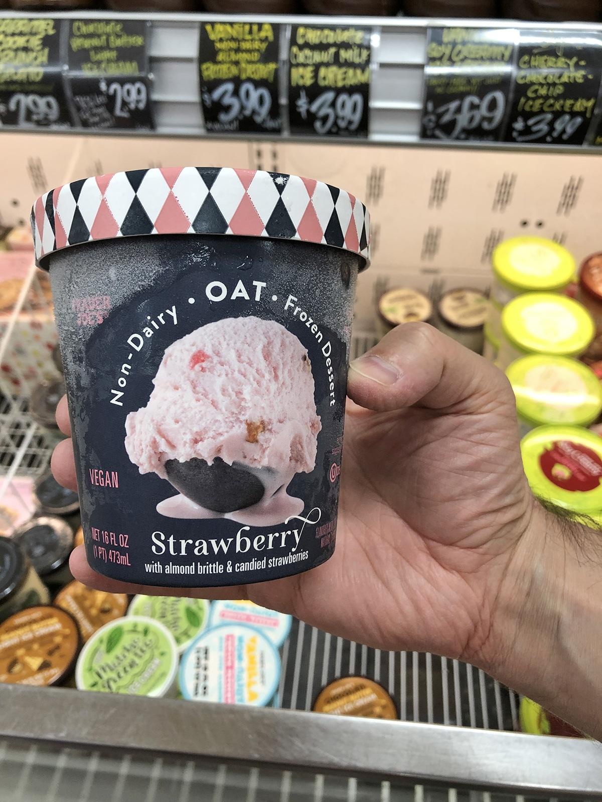 Hand holding strawberry ice cream.