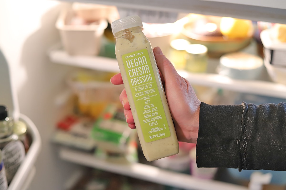 Hand holding Caesar dressing in front of refrigerator.