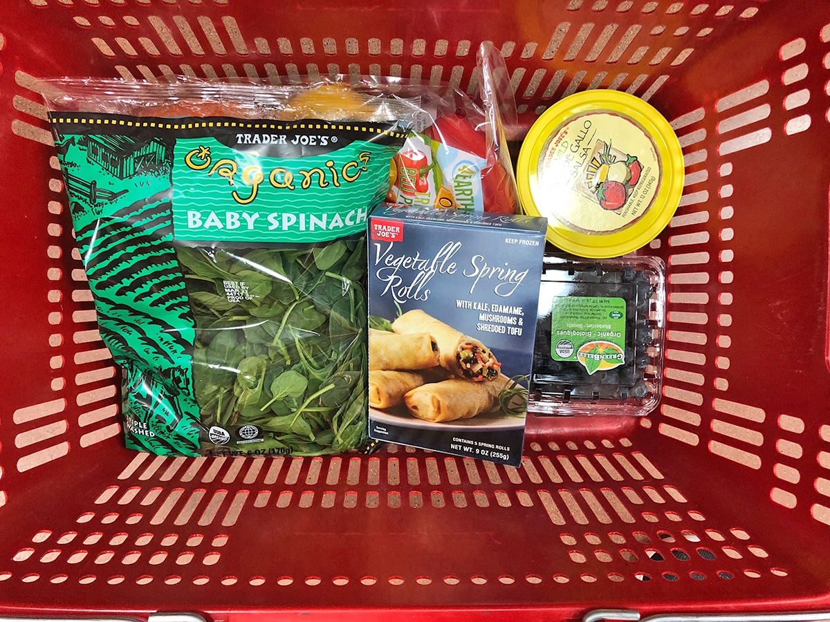 Shopping basket with vegetable spring rolls, spinach, and pico de gallo.