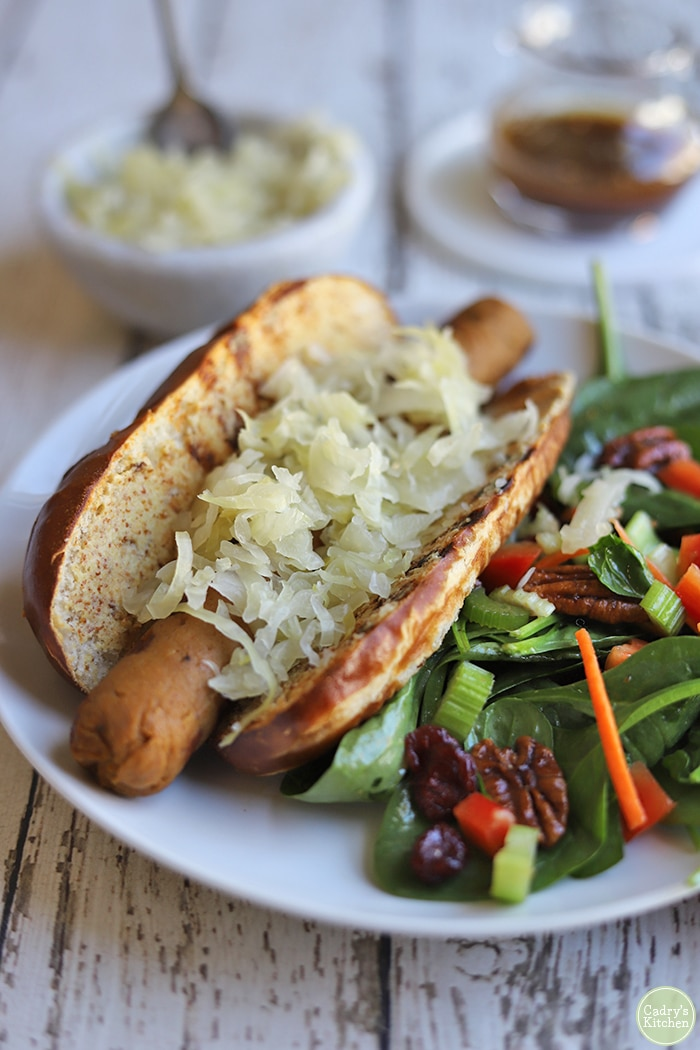 Vegan beer brat covered in sauerkraut with spinach salad as a barbecue side dish.