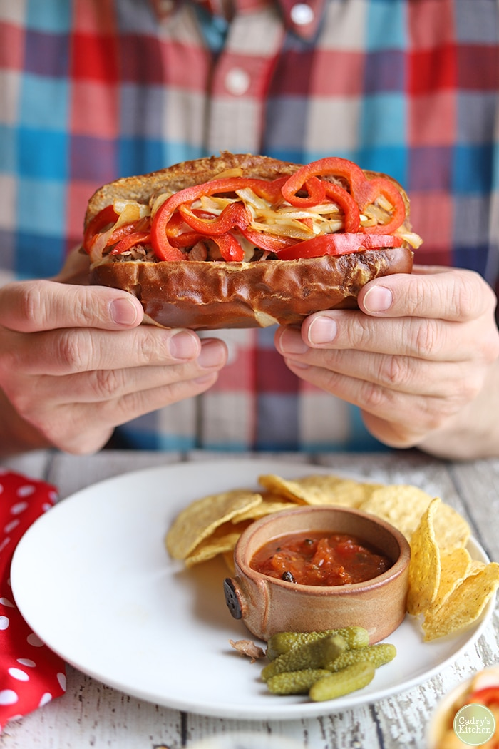 Hands holding jackfruit cheesesteak with peppers and onions.