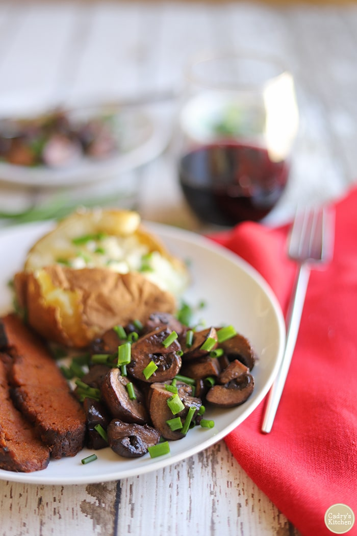 Red wine mushrooms with barbecue side dishes - air fryer baked potato and seitan steak.