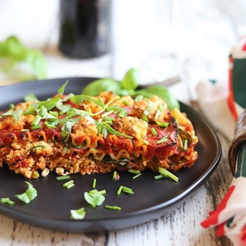 Vegetable lasagna with fresh basil & chives on black plate.