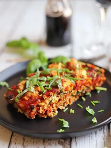 Vegan lasagna on black plate with fresh basil & chives.