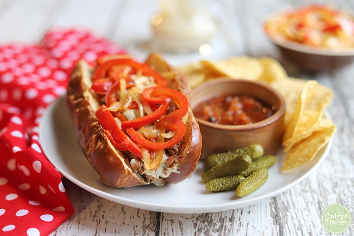 Vegan cheesesteak sandwich on plate with salsa and chips.