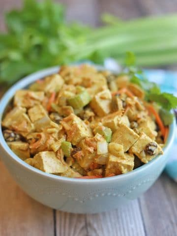 Bowl of tofu salad on table by celery stalk.