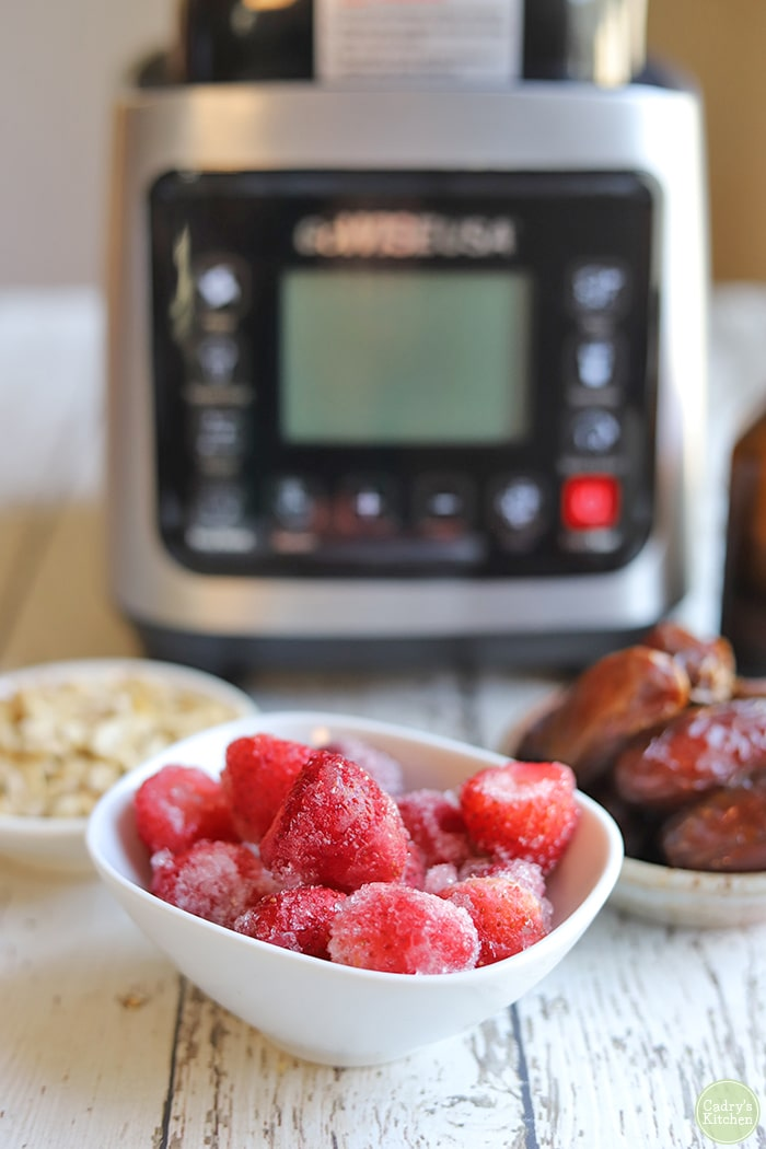 Bowl of frozen strawberries, dates, and raw cashews on table in front of blender.