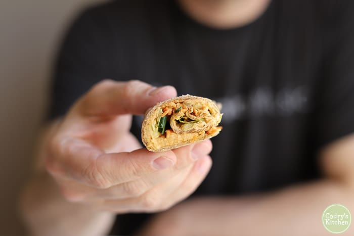 Hand holding buffalo hummus roll-up.