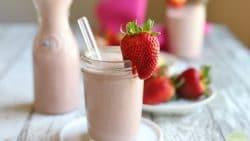 Vegan strawberry milk in glass with straw & strawberry.