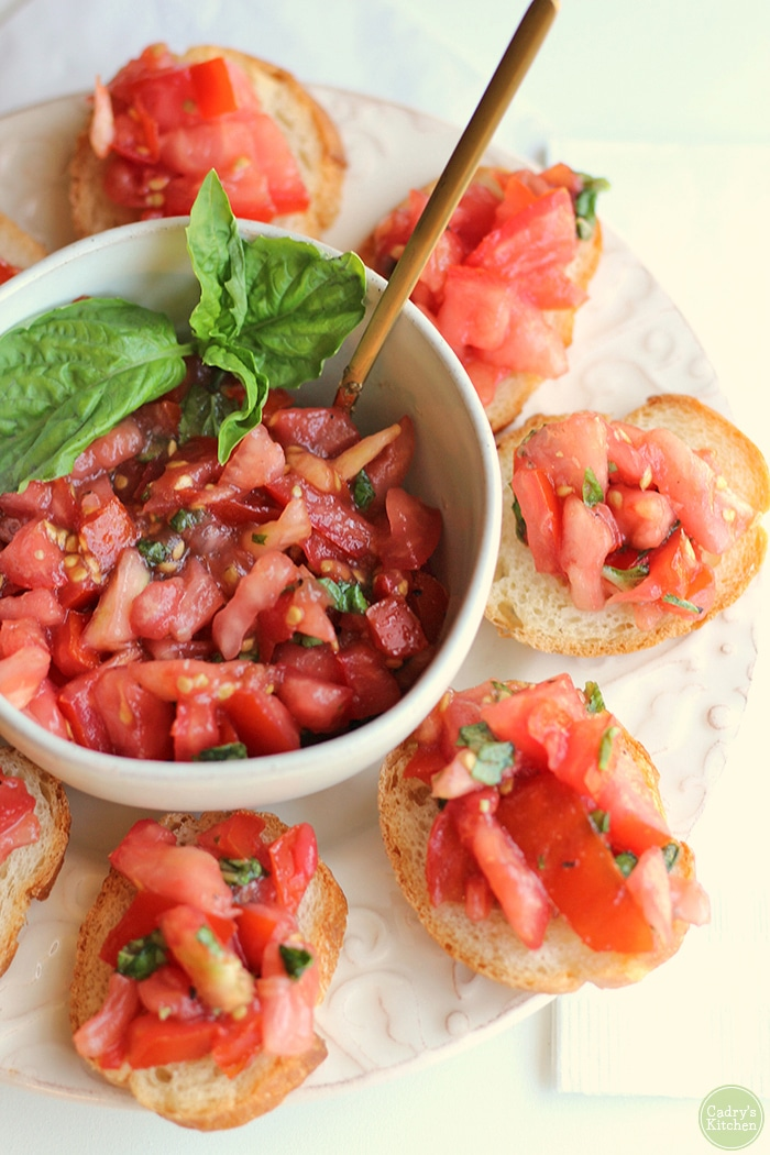 Bowl of bruschetta with basil & crostini on platter.